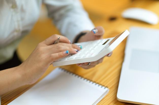 電卓を使用してカジュアルな女性をクローズアップ、背景がぼやけている電卓を使用して会計士