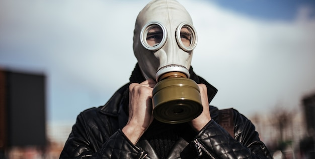 Close up. casual guy in a gas mask on a city background . photo with a copy-space