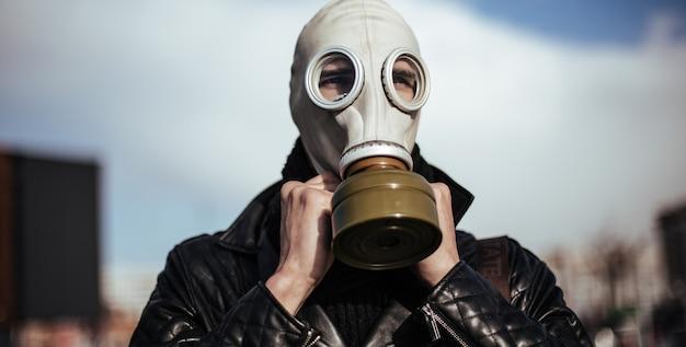 확대. 도시 배경에 가스 마스크에 캐주얼 남자. 복사 공간 사진