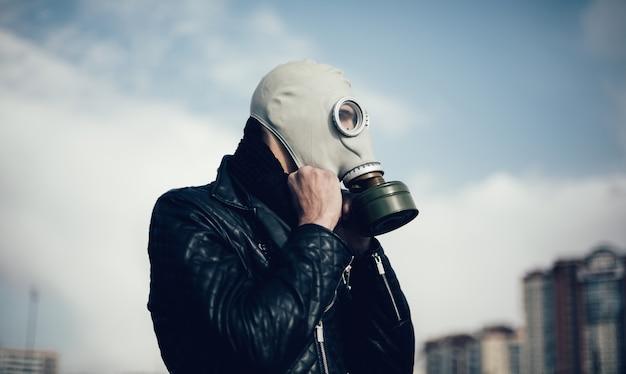 ガスマスクでカジュアルな男を閉じる