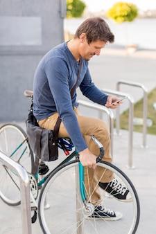 Крупный план случайный мужчина, закрепляющий свой велосипед