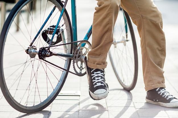 Крупный план случайный мужчина, сидящий на велосипеде