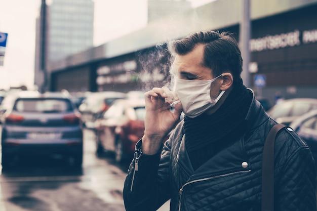 Закройте вверх. случайный мужчина курит стоя на улице