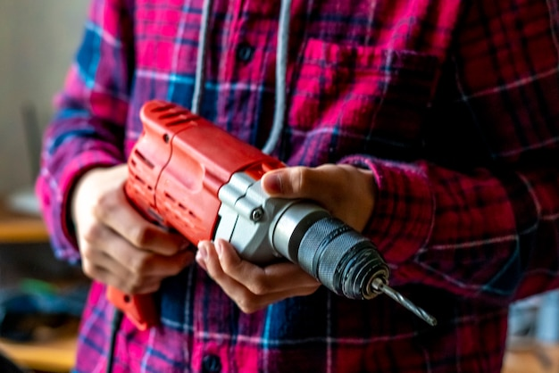 Close up casual worker holding electric drill and repair furniture at home f
