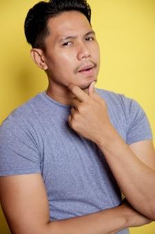 黄色の壁に分離されたあごに手で考えてカジュアルな若い男の笑顔を閉じる