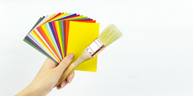 Close-up of catalog of paints with wood brush in woman hand, various color palette, samples for colour definition.