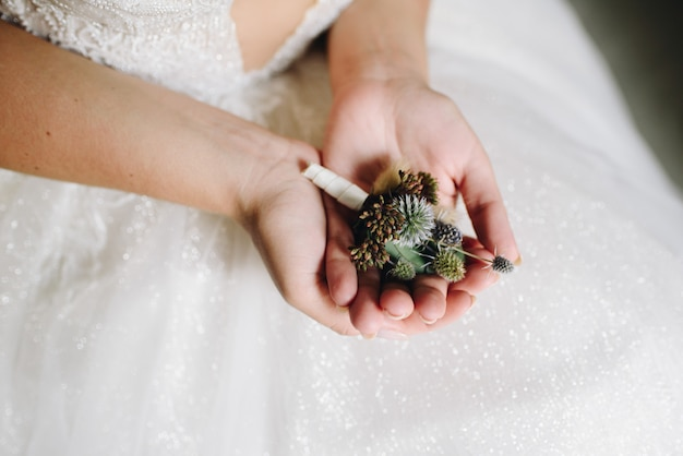 Close up of caucasian bride holding a delicate flower boutonniere on the day of her wedding