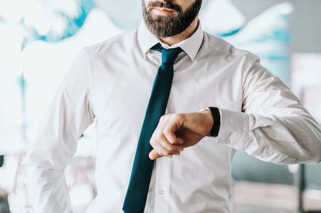 Close up of caucasian businessman looking at wristwatch while standing at office.