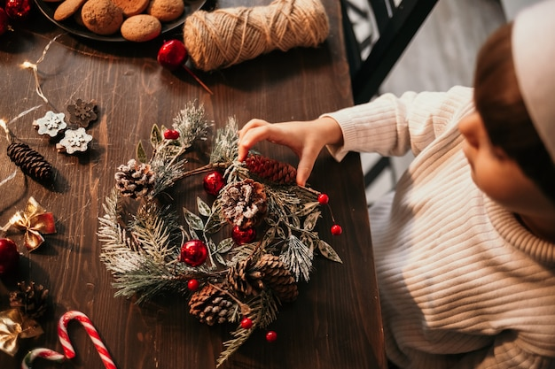 Close-up of a caucasian child sitting at a table and making a christmas tree wreath