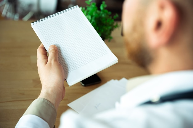 Close up of caucasian doctor consulting for patient explaining recipe for drug working in cabinet