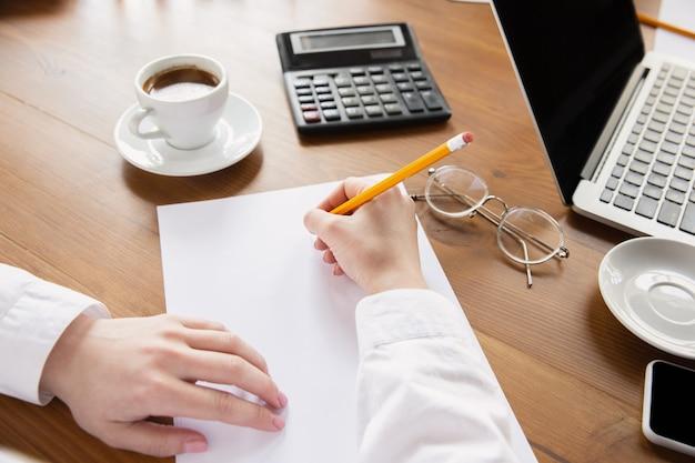 Chiuda in su delle mani femminili caucasiche che lavorano nella gente di affari dell'ufficio
