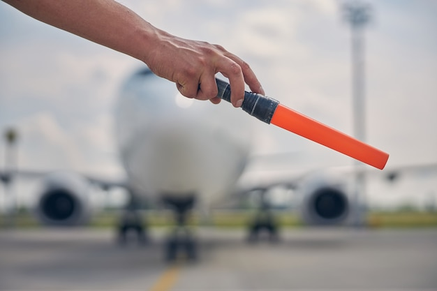 Close up of a caucasian male hand holding a marshaling wand in front of the plane