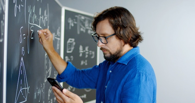 Close up of caucasian male teacher in glasses writing formulas and math laws on blackboard and looking at smartphone. educative mathematics lection. man lecturer using mobile phone as cribe.