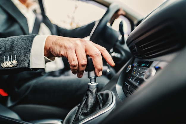 Close up of caucasian man holding hand on gearshift and changing speed.