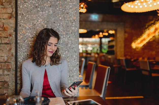 Крупным планом кавказской улыбается молодая женщина в ресторане