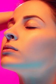 혼합 된 네온 불빛에 분홍색 스튜디오 배경에 고립 된 백인 여자의 초상화를 닫습니다. 아름다운 여성 모델. 인간의 감정, 표정, 판매, 광고, 패션의 개념. 아름다움.