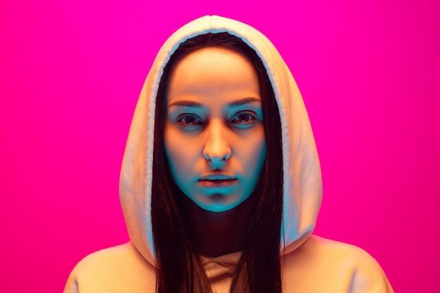 Close up ritratto di donna caucasica isolato su sfondo rosa studio in luce al neon mista. bellissimo modello femminile. concetto di emozioni umane, espressione facciale, vendite, pubblicità, moda. bellezza.