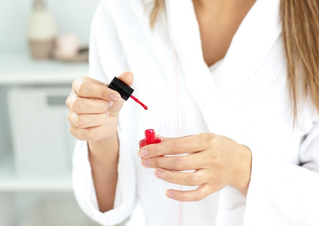 Close-up of a caucasian woman varnishing her fingernails in the bathroom