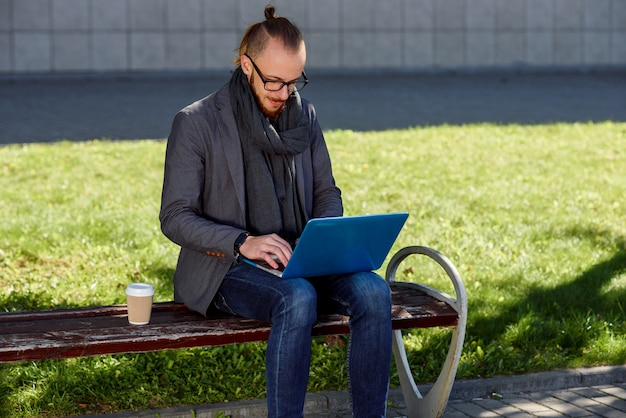 Close up of the caucasian young man with a beard sitting at the bench with laptop and cup of coffee. student sitting on the bench in the park and using laptop.