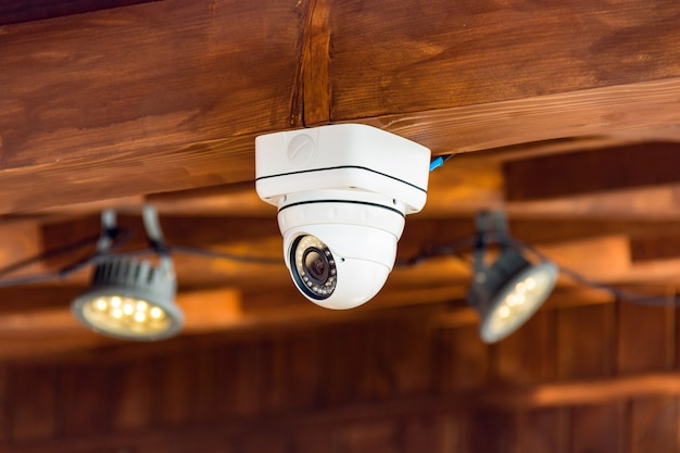 Close up of cctv security camera on the ceiling in the building Premium Photo