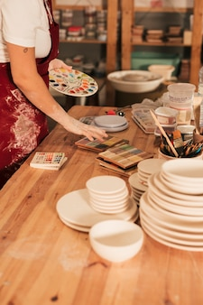 Close-up of ceramics palettes with stack of plates on wooden table