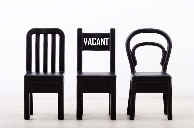 Close-up of a chair with text vacancy among black chairs in a row