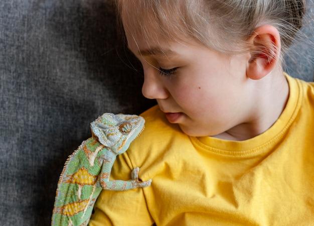 Primo piano camaleonte sulla spalla della ragazza