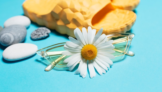 Close-up of chamomile flower on yellow sunglasses  background.