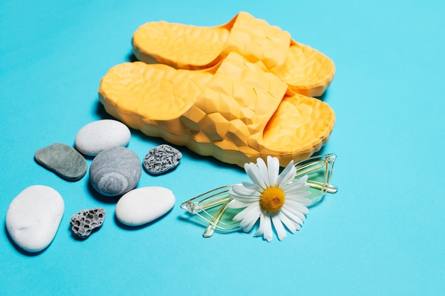 Close-up of chamomile flower on yellow sunglasses over blue background and slippers near pebbles. Premium Photo