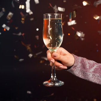 Close-up champagne glass with confetti