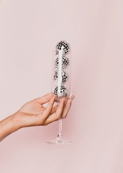 Close-up of champagne glass with disco balls