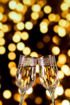 Close-up of champagne glasses on bokeh light background
