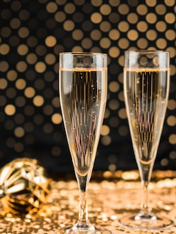 Close-up of champagne glasses on golden textile