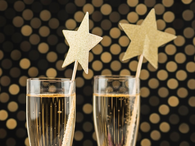 Close-up of champagne glasses with golden stars