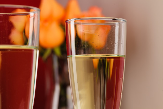 Close up of champagne glasses with roses in a vase