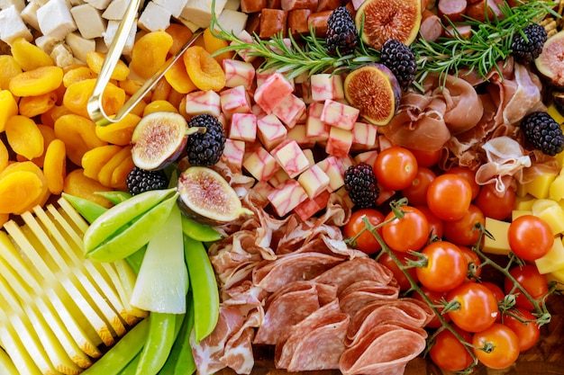 Close up of charcuterie board with cheese, fig, meat and crackers.