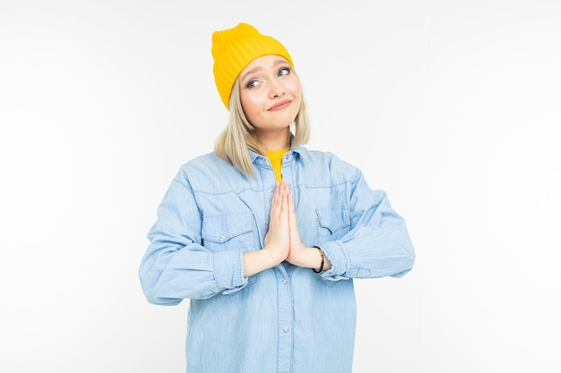 Close-up of a charming blonde dressed in casual style asking to buy something on a white background isolated with copy space