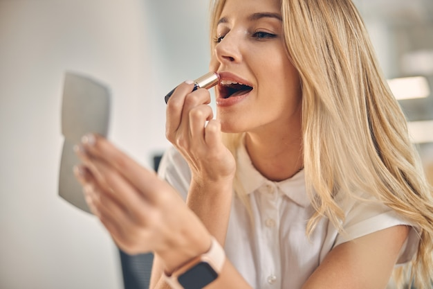 Close up of charming blonde lady looking in the mirror and smiling while doing makeup