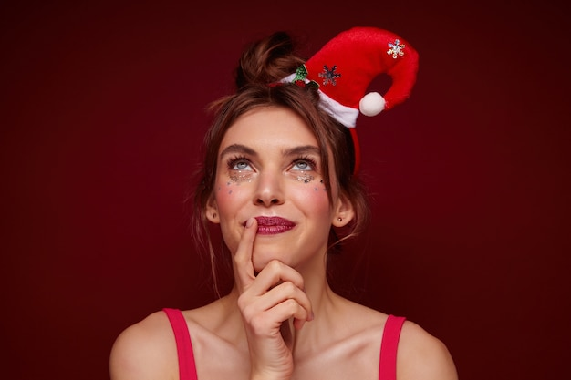 Close-up of charming blue-eyed young brunette lady with festive makeup wearing santa hat and looking dreamily upwards with pleasant smile, making new year wish