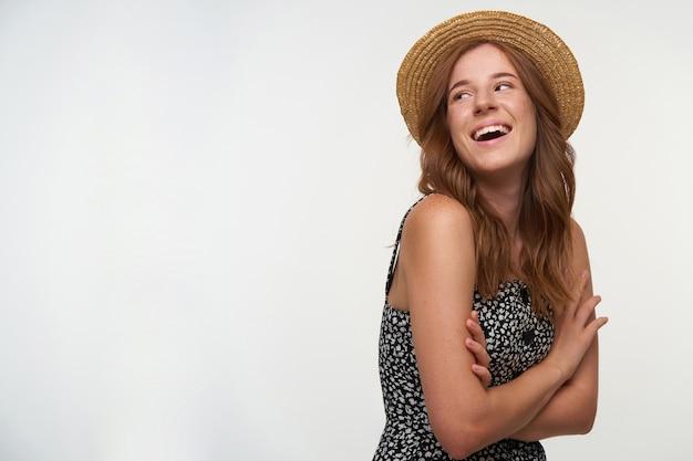 Close-up di affascinante allegra giovane donna rossa con riccioli in piedi su sfondo bianco con le mani giunte, ridendo allegramente e gettando indietro la testa, indossando abiti estivi e cappello di paglia