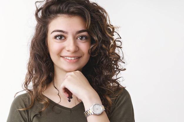 Крупный план очаровательной женственной армянской молодой кудрявой девушки с макияжем смотреть прикосновение к подбородку, нежно улыбаясь, белые здоровые зубы, стоя в приподнятом настроении, слушать интересную историю