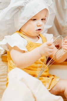 Close-up of a charming pretty grimy one-and-a-half-year-old girl, a cook holding a metal whisk for kneading dough. concept of studying the properties of materials in childhood