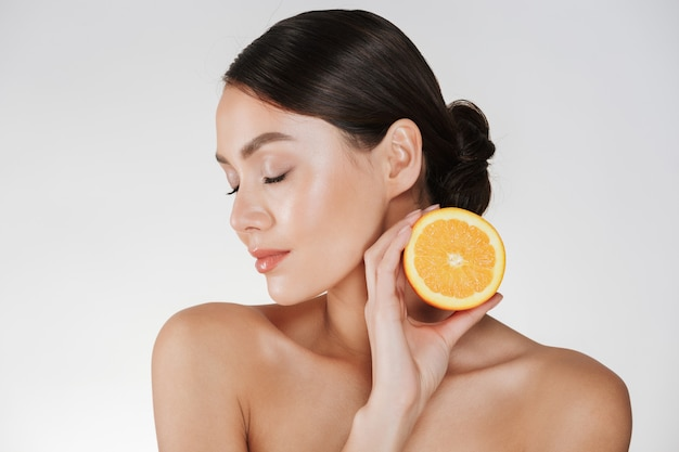 Close up of charming woman with soft fresh skin holding juicy orange, having detox isolated over white
