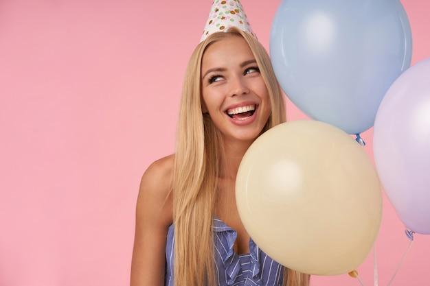 Primo piano di affascinante giovane femmina bionda che osserva da parte e sorridente ampiamente, in posa in mongolfiere multicolori in abito estivo blu e cappello di compleanno, isolato su sfondo rosa