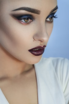 Close up of charming young lady with healthy skin and beautiful professional make up in studio