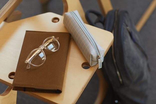 Close-up of checkered pencil case, brown notepad and eyeglasses on wooden chair in university room