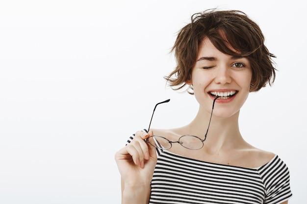 Primo piano della donna sorridente sfacciata che sbatte le palpebre giocosamente e morde il tempio degli occhiali