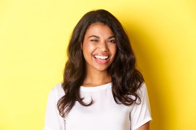 Primo piano di una ragazza afroamericana allegra, che fa l'occhiolino e sorride alla telecamera, consigliando qualcosa di buono, in piedi su sfondo giallo