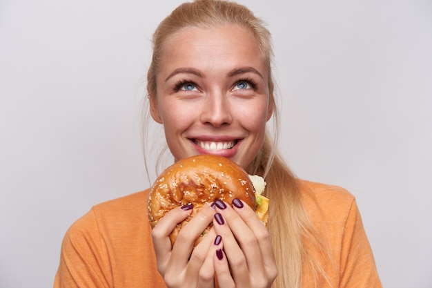 Close-up of cheerful blue-eyed young blonde female with big tasty hambuger looking happily upwards and smiling widely, dressed in casual clothes while posing over white background