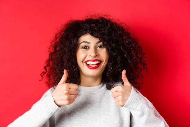 Close up of cheerful caucasian woman showing thumbs up in approval, smiling pleased, like and praise something good, standing on red wall.